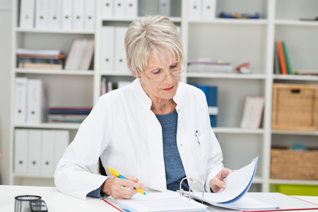 healthcare office: Elderly businesswoman working at her desk at the office reading through notes in a binder Stock Photo