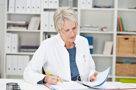 Oudere zakenvrouw werken op haar bureau in het kantoor door te lezen notities in een bindmiddel Stockfoto