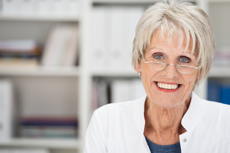Portrait of a beautiful friendly senior grey-haired lady wearing glasses posing in an office looking at the camera with a lovely smile