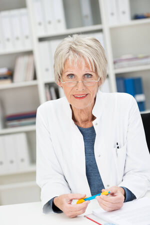 observant: Observant senior businesswoman sitting at her desk watching the camera with an intent expression over the top of her reading glasses