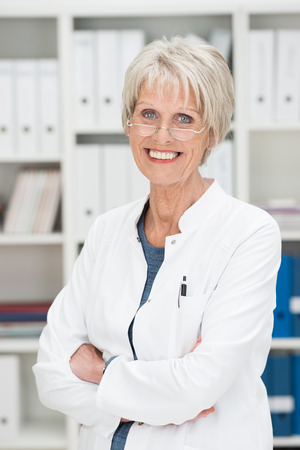 Smiling successful senior businesswoman standing with folded arms in her office looking at the camera over her reading glasses photo