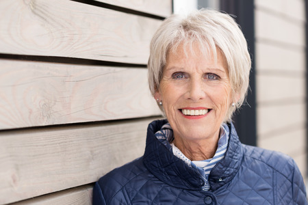 the elderly residence: Confident fashionable senior lady in a stylish high necked jacket standing leaning against a wooden building smiling at the camera Stock Photo