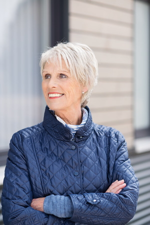 the elderly residence: Confident friendly stylish senior woman standing wearing a high necked jacket with folded arms outside her house looking to the side with a smile Stock Photo