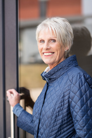 Smiling senior woman exiting her house pausing with her hand on the glass door to smile at the camera