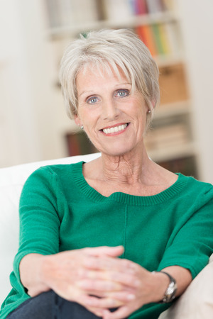 Portrait of an attractive senior woman sitting in a relaxed position on a sofa in her living room smiling at the camera with a friendly smile photo