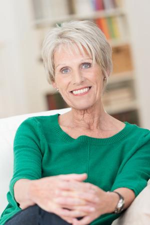 old age: Ritratto di una donna attraente senior seduto in una posizione rilassata su un divano nel suo salotto sorridendo alla telecamera con un sorriso amichevole