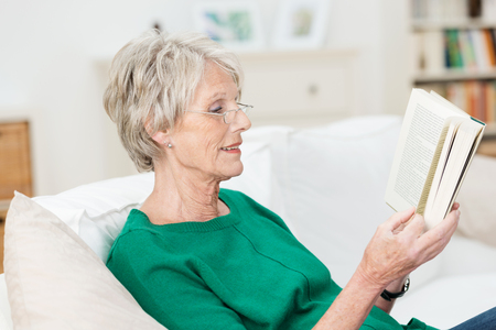 Attractive elderly woman reading a book at home smiling quietly to herself as she relaxes on a comfortable couch photo