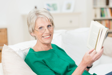Relaxed happy senior woman enjoying a book as she sits on a comfortable sofa in her living room photo