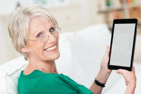 home computer: Attractive senior woman using a tablet computer relaxing on a sofa at home turning to smile at the camera - the screen blank is visible to the viewer Stock Photo