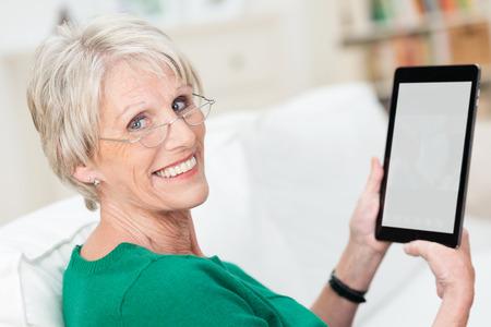 person computer: Attraktive �ltere Frau mit einem Tablet-Computer entspannt auf einem Sofa zu Hause drehen, um in die Kamera l�cheln - der Bildschirm leer f�r den Betrachter sichtbar ist