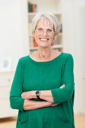 Relaxed confident beautiful senior woman standing wearing her reading glasses with folded arms and a lovely warm friendly smile photo