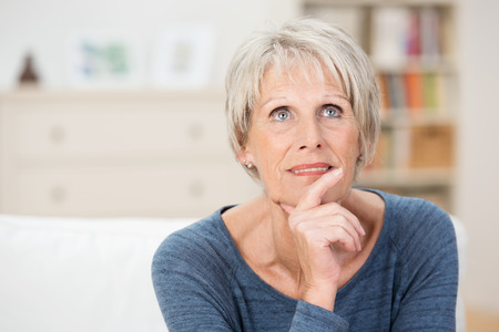 wistful: Wistful senior woman sitting thinking staring pensively up into the air as she reminisces on her life Stock Photo
