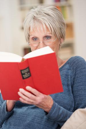 mujer leyendo libro: Mujer mayor que desgasta las gafas de lectura relajante con un libro de tapa dura de color rojo en un cómodo sillón en el salón de su casa