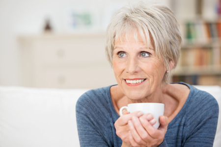 Elderly woman sitting daydreaming over a cup of aromatic coffee staring into the distance with a smile as she reminisces photo