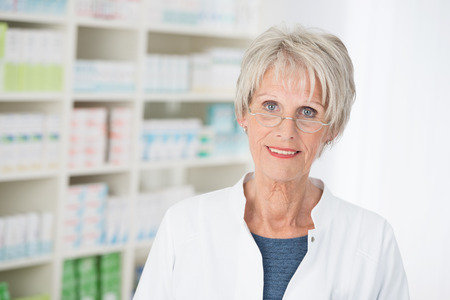 stocked: Senior lady wearing glasses working as an assistant or pharmacist in a pharmacy standing looking at the camera against a backdrop of fully stocked shelves