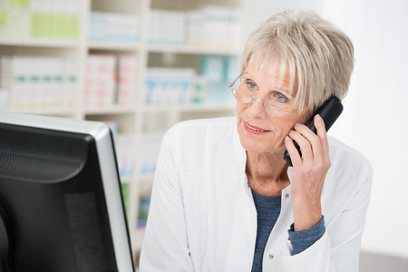 Elderly female pharmacist working in the pharmacy standing at her computer chatting on the phone listening to a patient talking photo