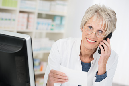 Smiling pharmacist checking up on a prescription that she is holding in her hand as she chats on the telephone to a doctor or patient photo
