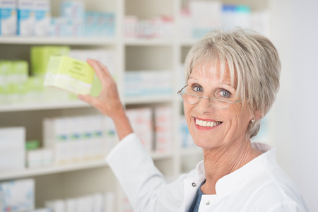 Smiling happy female pharmacist reaching for medication on the shelf and displaying it to the camera photo