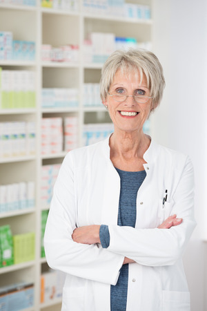 stocked: Attractive confident senior pharmacist standing with her arms folded giving the camera a beautiful friendly smile, stocked shelves behind her