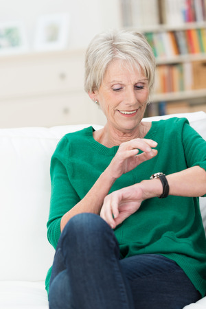 Beautiful elderly woman checking the time looking at her wrist watch as she relaxes on a sofa in her living room photo