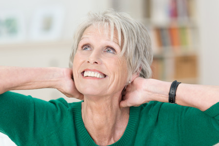 head home: Beautiful elderly lady with a radiant smile sitting with her hands clasped behind her head daydreaming as she stares up into the air