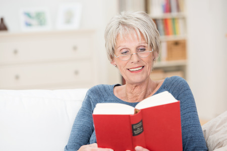 Horizontal portrait of a retired Caucasian amused woman reading an interesting book with red covers while sitting on the sofa at home