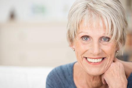 mujeres maduras: Cerrar un retrato facial de una mujer mayor que mira a la cámara con una sonrisa cálida y atenta expresión Foto de archivo