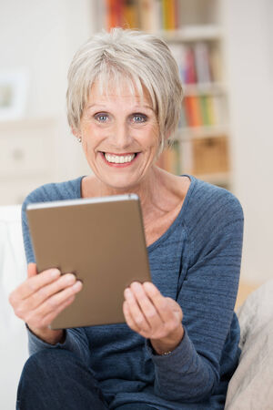 Vertical portrait of a blond Caucasian modern senior woman smiling cheerfully and wearing a casual blue long-sleeve T-shirt while sitting in the living holding a tablet PC photo