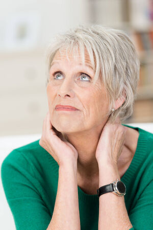 ponder: Worried upset senior woman looking to heaven for help with a grimace and look of desperation Stock Photo