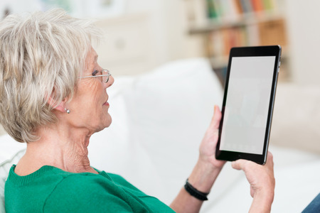 Senior lady relaxing at home on a sofa reading an e-book on her tablet, over the shoulder view with the blank screen visible