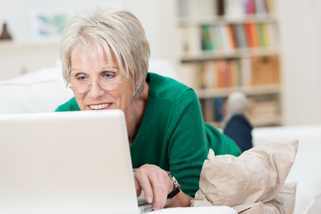 Tech savvy senior woman relaxing with a laptop at home lying on a sofa wearing her glasses and reading the screen Stock Photo