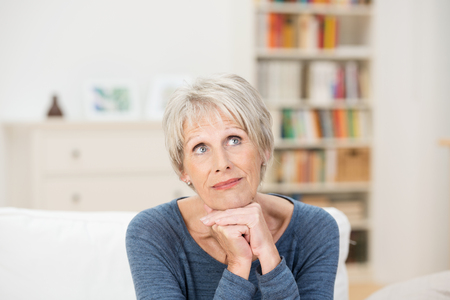 Elderly attractive woman sitting on a sofa in the living room reminiscing looking up into the air with a wistful expression photo