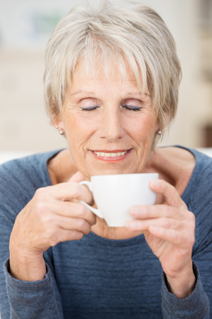 eye's closed: Attractive senior woman sitting savoring the aroma of a cup of coffee breathing in the smell with her eyes closed in bliss and a look of contentment Stock Photo