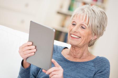 personas leyendo: Mujer mayor que sonr�e feliz mientras lee la pantalla en su tablet PC comprobando en sus contactos de redes sociales Foto de archivo