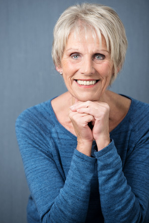 Attractive senior woman with blue eyes sitting with clasped hands looking directly at the camera with a beautiful smile photo