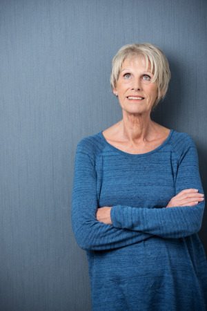 Elderly lady standing thinking standing against a blue background with her arms folded looking pensively up into the air, with copyspace photo