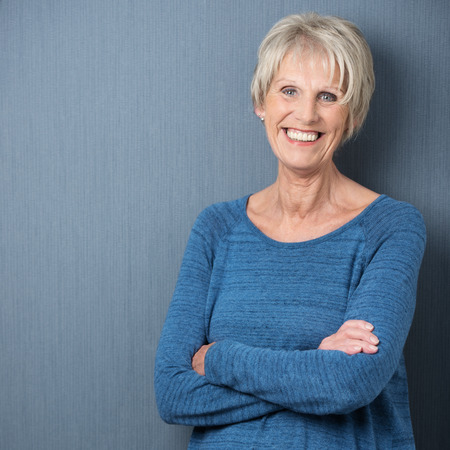 Happy confident attractive senior woman with blue eyes and a wide beaming smile standing with folded arms against a blue background with copyspace