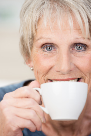 Elderly woman enjoying a relaxing cup of tea smiling over the rim of the cup as she looks directly into the lens photo