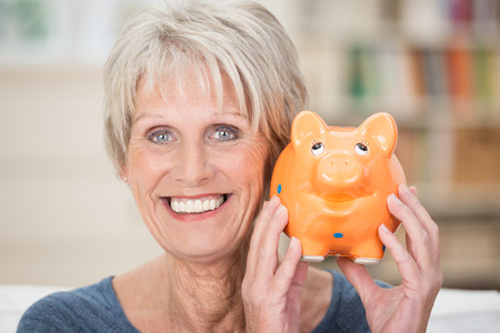 Excited senior woman holding up her piggy bank smiling in anticipation of a planned vacation or purchase to be paid for from her nest egg and savings photo