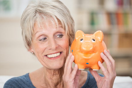 Charismatic elderly woman holding up a piggy bank looking sideways at is as she smiles while contemplating what to do with her savings photo