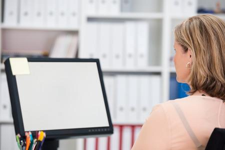 looking at view: Businesswoman seduto alla sua scrivania in ufficio, lavorando su un monitor desktop con lo schermo bianco vuoto visibile per lo spettatore