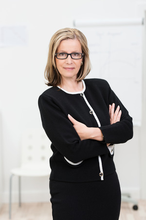 austere: Confident austere middle-aged businesswoman wearing glasses standing with her arms folded looking intently at the camera