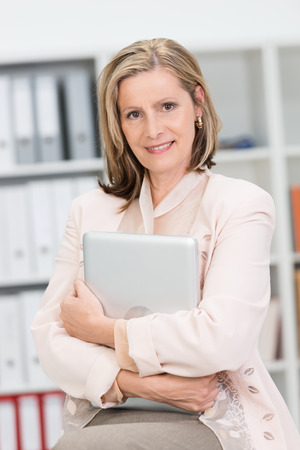 clutching: Confident attractive middle-aged businesswoman sitting on a stool in the office clutching her laptop to her chest with a friendly smile Stock Photo