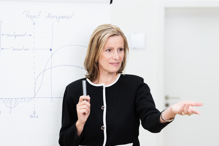 Attractive middle-aged businesswoman giving a presentation or in house training session gesturing with her hand to invite questions from the audience Imagens