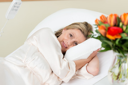 Smiling attractive female patient lying in a hospital bed cuddling down into the pillows as she smiles bravely at the camera, view past roses on the side table photo
