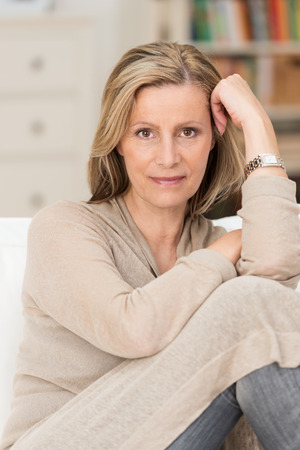 knees up: Serious thoughtful middle-aged woman sitting with her knees up on a sofa staring directly at the camera