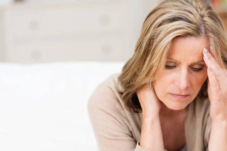 mujer pensando: Mujer que sufre de estrés o un dolor de cabeza con una mueca de dolor mientras sostiene la parte posterior de su cuello con la otra mano a la sien, con copyspace