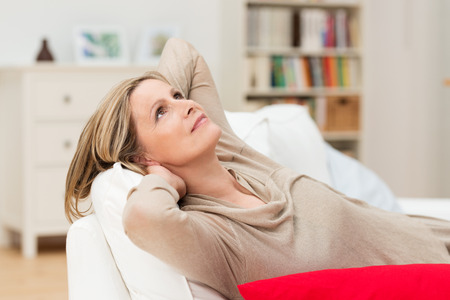 Housewife relaxing at home daydreaming reclining on the sofa with her hands clasped behind her head staring up into the air with a faraway expression