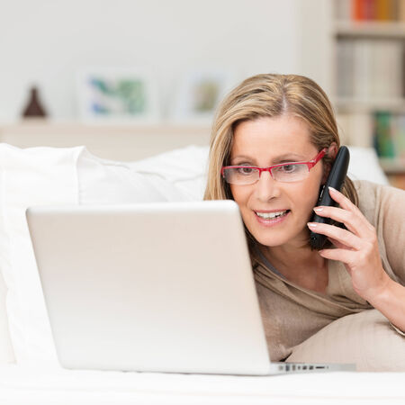 boomer: Attentive woman wearing glasses talking on her mobile phone as she lies on her sofa reading information on the screen of her laptop