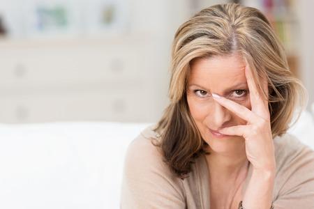 Speelse aantrekkelijke blonde vrouw peering tussen haar vingers op de camera met een glimlach als ze ontspant thuis, met copyspace Stockfoto